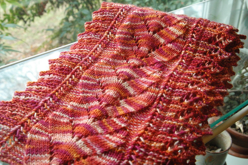 A multicolor red scarf knitted in a lace pattern