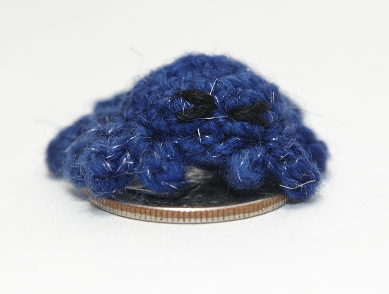 Crocheted crab on a quarter