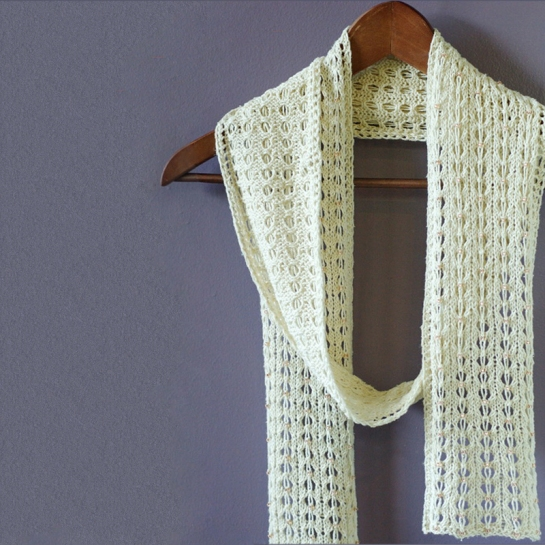 An ivory beaded scarf on hanger
