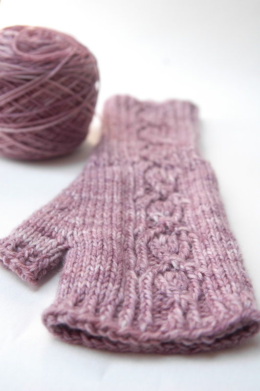 A pink hand knit fingerless mitt