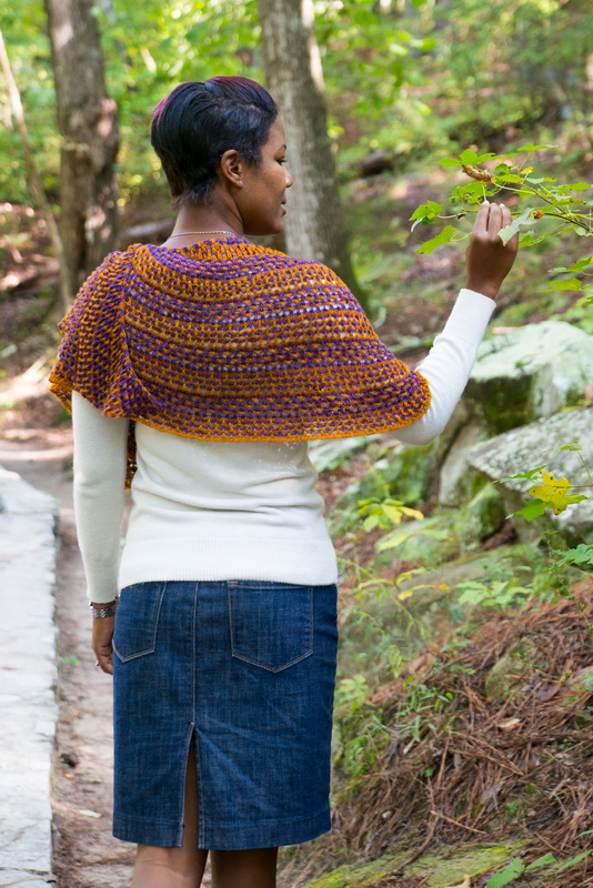 Love Child, lace combined with two colors and slipped stitches create this knitted shawl by Barbara Benson